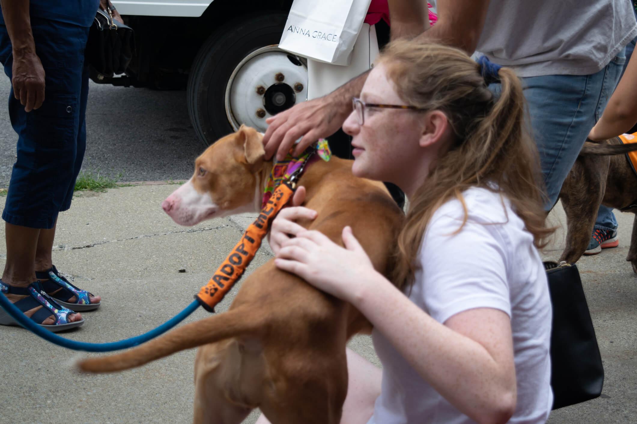 A woman hugs a shelter pet at an animal adoption event